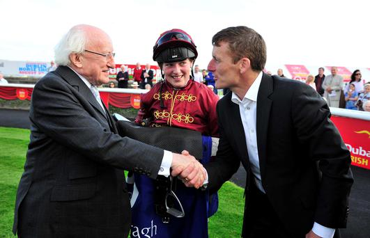 President Michael D Higgins congratulates trainer Johnny Murtagh after his daughter Caroline (centre) had ridden 20/1 outsider Jocular to victory in the DoneDeal Apprentice Derby at the Curragh