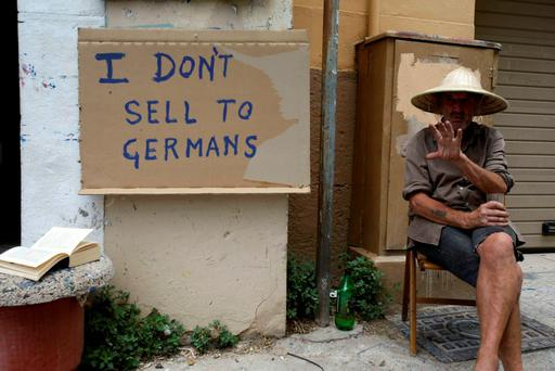 Tom McGrath, a vendor originally from Belfast who has lived in Greece for the last 20 years, sits next to a satirical sign written by him in the Plaka tourist district of Athens yesterday. Photo: Thanassis Stavrakis
