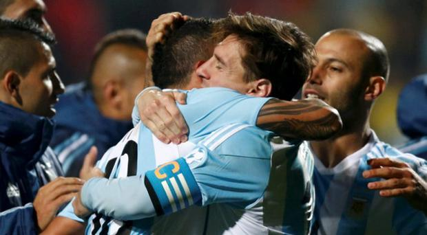 Argentina's Lionel Messi (R) and Argentina's Tevez hug after defeating Colombia in penalties following regulation play in their Copa America 2015 quarter-final
