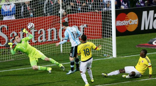 Colombia's goalie David Ospina blocks a header from Argentina's Lionel Messi (10) as Colombia's Juan Zuniga (18) and Cristian Zapata looks on