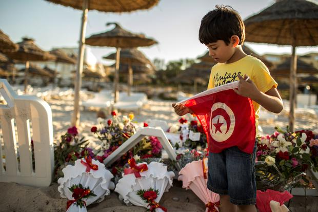 A boy holds a Tunisian flag as he stands near bouquets of flowers laid at the beachside
