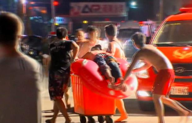 In this screen grab taken from ETTV, an injured concert spectator is treated after an accidental explosion during a music concert at the Formosa Water Park in New Taipei City, Taiwan (ETTV via AP)