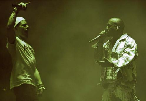 English comedian Simon Brodkin (L), playing his character Lee Nelson, interrupts American singer Kanye West has he performs on the Pyramid Stage at the Glastonbury Festival of Music and Performing Arts on Worthy Farm near the village of Pilton in Somerset, South West England, on June 27, 2015.
