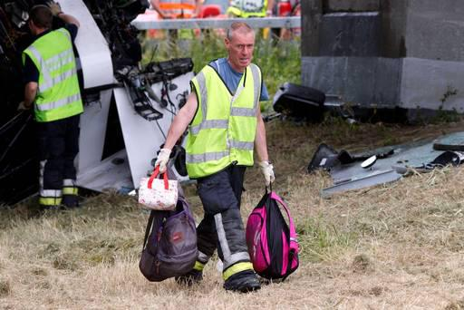 A rescue services worker carries students' backpacks at the site where a bus carrying 34 British schoolchildren crashed off the E40 highway in Middelkerke, Belgium. AFP PHOTO / BELGA / NICOLAS MAETERLINCK.