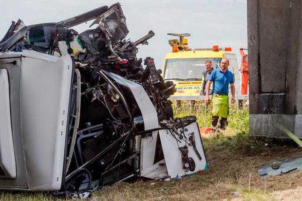 A bus, which carried British schoolchildren, lays on its side under an overpass on a motorway in Middlekerke, Belgium, Sunday. (AP Photo/Geert Vanden Wijngaert)