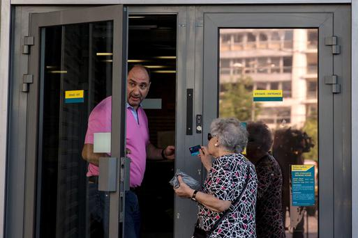 A woman talks to a bank employee outside a National Bank branch in Athens, Greece June 28, 2015. Greece's European partners shut the door on extending a credit lifeline to Athens, leaving the country facing a default that could push it out of the euro and cause ripple effects across the European economy and beyond. REUTERS/Marko Djurica