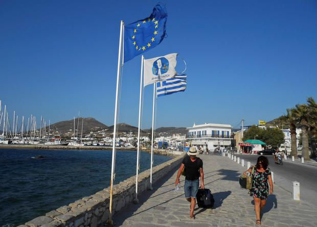 Tourists make their way past a European Union flag and a Greek national flag at the seaside of the island of Paros, Greece June 26, 2015. A rise in consumer taxes on Greek islands' goods and services is one of the sacrifices creditors are seeking from Athens to unlock bailout funds that will allow Greece to remain in the euro. The tax hike is one of the sticking points thwarting a deal and prompting Prime Minister Alexis Tsipras to call a July 5 referendum on the bailout terms. Yet even before the vote, Greece is likely to default on a debt payment, setting off a financial crisis that could damage an upcoming tourist season expected to be one of the most vibrant in years. Picture taken June 26, 2015. REUTERS/Matthias Williams