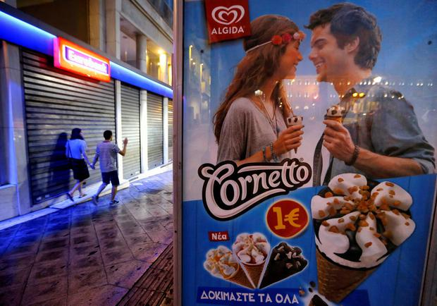 A couple walks past a Eurobank branch near an advertisement at a bus stop in Athens, Greece June 28, 2015. REUTERS/Yannis Behrakis