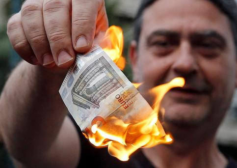 An anti-austerity protester burns a euro note during a demonstration outside the European Union offices in Athens