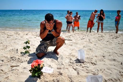 A man prays after laying flowers on the beach in Sousse, Tunisia, where 38 people, including three Irish tourists, were killed in a terrorist attack