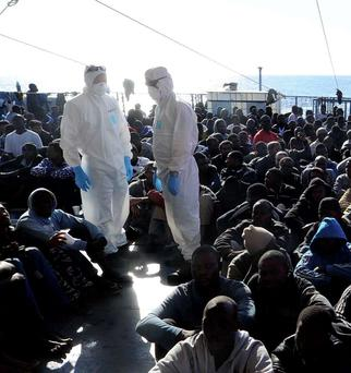 Hundreds of migrants sit on the deck of the LÉ Eithne after being rescued yesterday