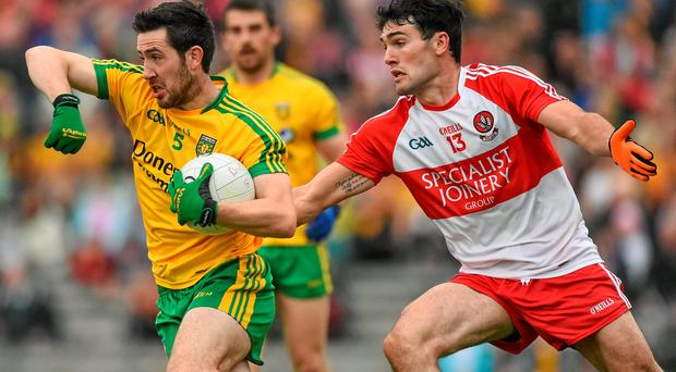 Donegal's Mark McHugh attempts to get away from Danny Heavron of Derry during their Ulster SFC in Clones SPORTSFILE