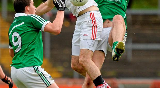 Tyrone's Justin McMahon in action against Geroid Hegarty and Tom Lee of Limerick in their clash at Healy Park yesterday OLIVER McVEIGH/SPORTSFILE