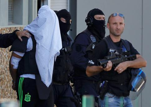 Delivery driver Yassin Salhi is escorted by heavily armed and masked police officers from his house in Saint-Priest, near Lyon, France