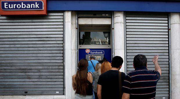 A man reacts as people line up to withdraw cash from an ATM outside a Eurobank branch in Athens, Greece in this June 28, 2015 file photo
