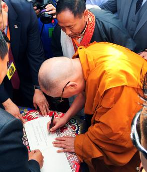 Dalai Lama signs an inauguration declaration as he opens a new Buddhist community centre in Aldershot, Hampshire credit: Ben Mitchell/PA Wire