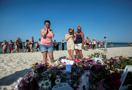 A family reacts beside flowers laid on the beach of the Imperial Marhaba resort, which was attacked by a gunman, in Sousse, Tunisia, June 28, 2015. REUTERS/Zohra Bensemra