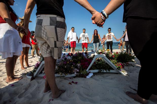 People hold hands as they pray in a circle around bouquets of flowers laid in tribute on the beach of the Imperial Marhaba resort, which was attacked by a gunman, in Sousse, Tunisia, June 28, 2015. REUTERS/Zohra Bensemra