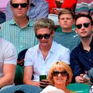 Niall Horan of the band One Direction (C) gestures as he wattches Serbia's Novak Djokovic return to Germany's Philipp Kohlschreiber during their men's singles first round match on day one of the 2015 Wimbledon Championships at The All England Tennis Club in Wimbledon