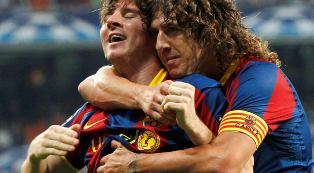 Barcelona's Lionel Messi celebrates with teammate Carles Puyol (R) after scoring against Real Madrid during their Champions League semi-final first leg in 2011