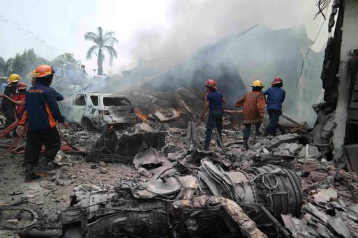 Firemen attempt to extinguish the fire surrounding the wreckage of an Indonesian military transport plane after it crashed in the North Sumatra city of Medan, Indonesia REUTERS/Irsan Mulyadi/Antara Foto