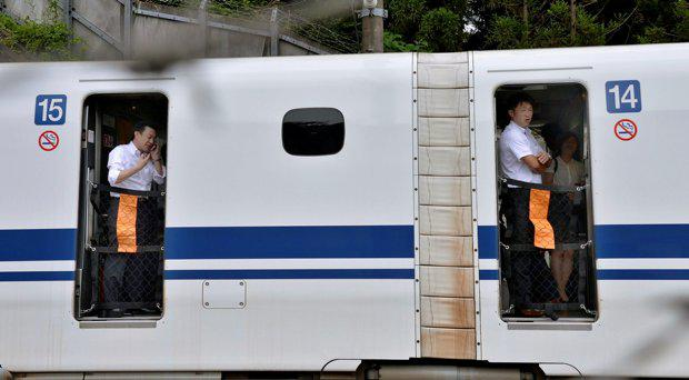 Passengers stand inside a Shinkansen bullet train which made an emergency stop in Odawara, west of Tokyo Tuesday, June 30, 2015. A passenger on the Japan's high-speed bullet train tried to set himself or herself on fire Tuesday, causing smoke to fill the carriage and forcing the train to stop, Japans transport ministry said. (Kyodo News via AP Photo) JAPAN OUT, MANDATORY CREDIT