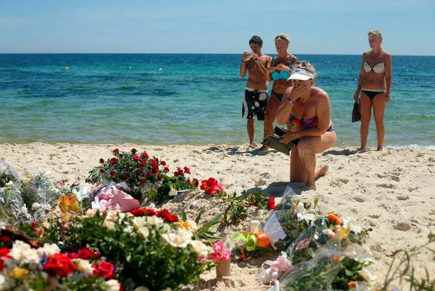 Tourists lay flowers on a beach in Sousse where 38 people where killed last Friday Credit: Steve Parsons