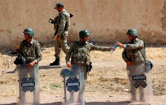 A Turkish soldier shares a bottle of water with his comrade as they stand guard near the Mursitpinar border gate in Suruc, bordering with Syrian town of Kobani, Sanliurfa province. Photo: Reuters