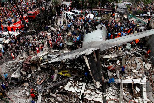 Rescue workers at the scene where the Hercules C-130 crashed into a small hotel in the city of Medan, on the island of Sumatra
