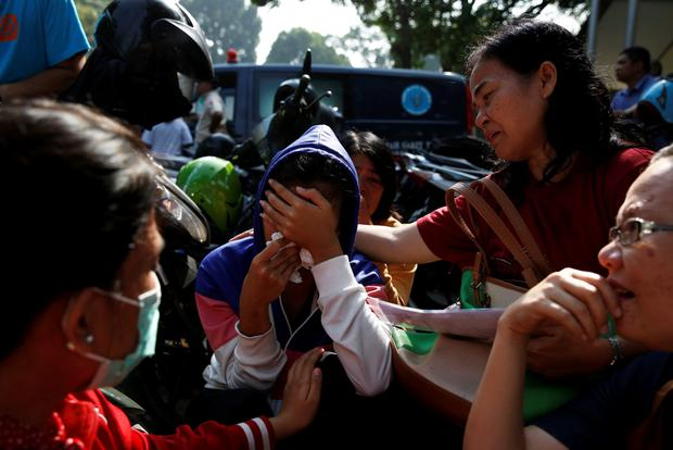 Family members of victims of an Indonesian military C-130 Hercules transport plane that crashed into a residential area, cry outside Adam Malik hospital in the North Sumatra city of Medan, Indonesia, July 1, 2015 REUTERS/Beawiharta