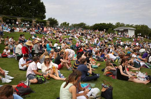 Spectators enjoying the weather, during day one of the Wimbledon Championships at the All England Lawn Tennis and Croquet Club, Wimbledon. Philip Toscano/PA Wire