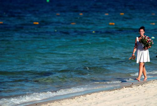 A woman carries flowers on the beach near the RIU Imperial Marhaba hotel in Sousse, Tunisia, as British holidaymakers defy the terrorists and continue to stay in Sousse despite the bloodbath on the beach: Steve Parsons/PA Wire