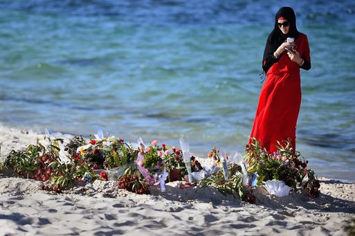 SOUSSE, TUNISIA - JUNE 30: A woman looks at flowers laid on Marhaba beach in Sousse, where 38 people were killed in a terror attack. Photo by Jeff J Mitchell/Getty Images