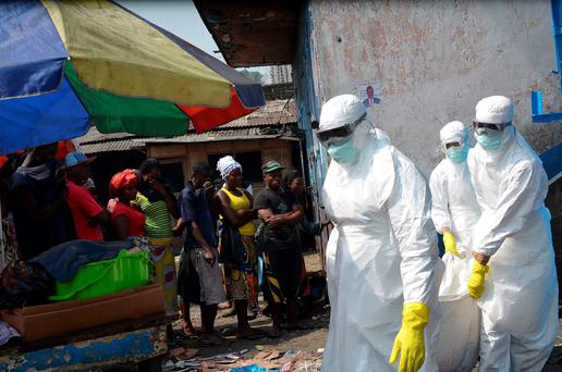 Red Cross workers in protective suits remove the body of an Ebola victim in Monrovia.