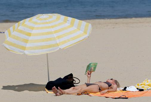 A woman sunbathes on a beach along the Bassin d'Arcachon Sea in Arcachon, near Bordeaux. Photo: Reuters/Regis Duvignau