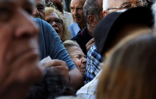 A pensioner is crushed as she waits outside a National Bank branch to receive part of her pension in Athens yesterday