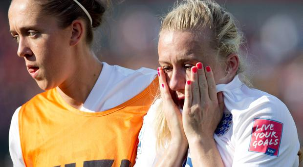 England's Josanne Potter, left, and Laura Bassett leave the field after a 2-1 loss to Japan during a semifinal in the FIFA Women's World Cup