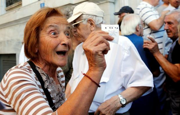 A pensioner reacts as she obtains a priority ticket to get part of her pension outside a National Bank branch in Athens, Greece, July 1, 2015