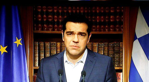 Greek Prime Minister Alexis Tsipras is seen on a television monitor while addressing the nation in Athens, Greece July 1, 2015