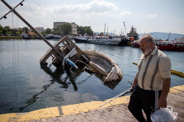 A man walks past a capsized ship at a marina in the town of Elefsina, near Athens, Greece June 30, 2015. In a poll released on July 1, 54 percent of Greeks showed that they would heed the advice of leftist Greek Prime Minister Alexis Tsipras and vote in the Greek referendum against new tough conditions for financial aid in the hope that creditors would compromise. Picture taken June 30, 2015. REUTERS/Marko Djurica TPX IMAGES OF THE DAY