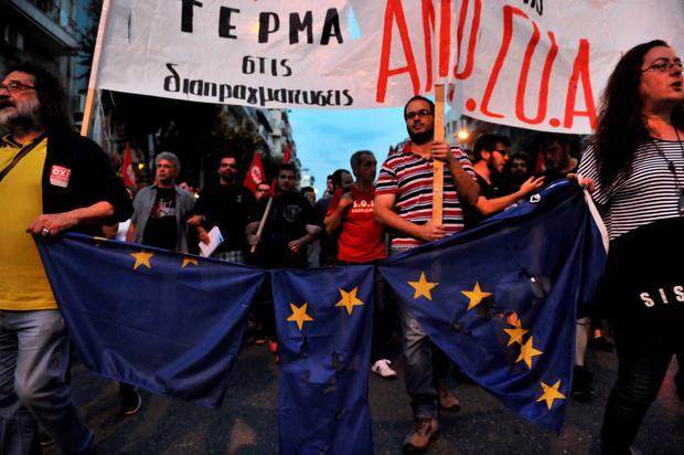 Protestors march holding a torn European Union flag during a demonstration for the