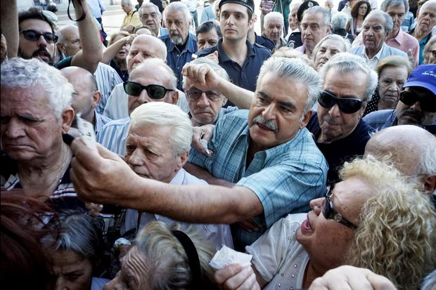 ATHENS, GREECE - JULY 1: Pensioners line up outside a National Bank branch on July 1, 2015 in Athens, Greece. Bank branches around Greece are opened on Wednesday to allow pensioners to receive a small part of their benefits. Greece's last-minute overtures to international creditors for financial aid on Tuesday were not enough to save the country from becoming the first developed economy to default on a loan with the International Monetary Fund. (Photo by Milos Bicanski/Getty Images) *** BESTPIX ***