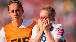 England's Jo Potter (L) consoles teammate Laura Bassett after she scored an own-goal in the last minutes of the game giving Japan the win in their semifinal match at the FIFA Women's World Cup