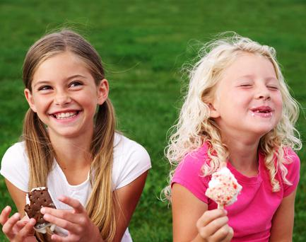 Two laughing sisters enjoy ice cream treats.