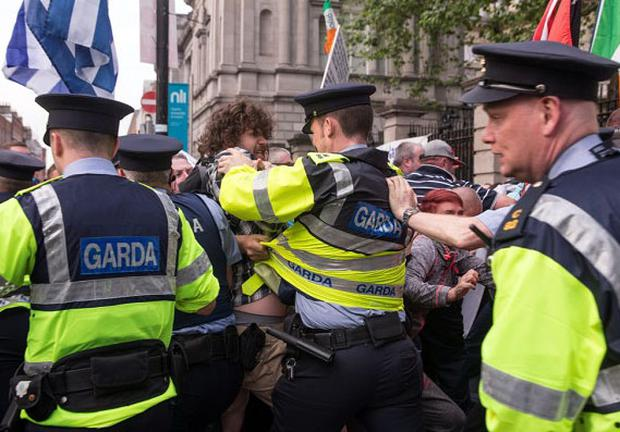 Gardai struggle with protesters outside the Dail