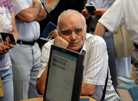 A man waits for part of his pension at a bank in Crete yesterday