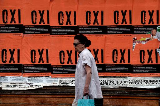 A woman walks past posters reading 'NO' in Athens ahead of the referendum