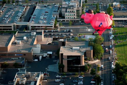 The Bank of American Fork piggy bank balloon flies through the air before crash landing near Utah Valley Regional Medical Center during America's Freedom Festival Balloon Fest on Thursday, July 2, 2015, in Provo, Utah. (Grant Hindsley/The Daily Herald via AP)