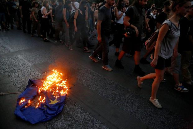 Demonstrators burn a European Union flag during a rally supporting the no vote for the upcoming referendum outside European Union office in Athens, Thursday, July 2, 2015. (AP Photo/Petros Karadjias)