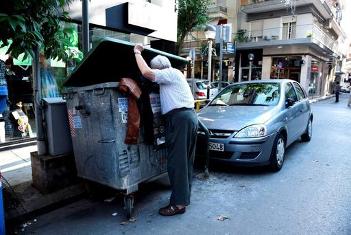 An elderly man finds old clothes as he searches in a garbage bin in the northern Greek port city of Thessaloniki, Thursday, July 2, 2015. (AP Photo/Giannis Papanikos)
